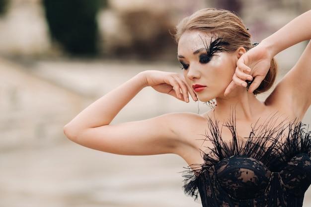黒のウェディングドレスを着たスタイリッシュな花嫁が、古代フランスの都市アヴィニョンでポーズをとっています。美しい黒のドレスを着たモデル。プロヴァンスでの写真撮影。