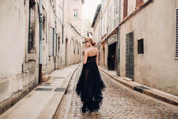 Стильная невеста в черном свадебном платье позирует в старинном французском городе авиньон.
