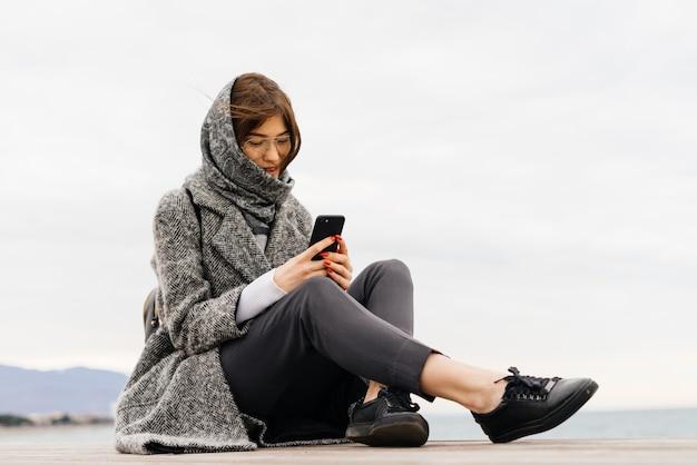 Стильная темноволосая молодая девушка в очках, с платком на голове сидит на улице, пишет сообщение на смартфон