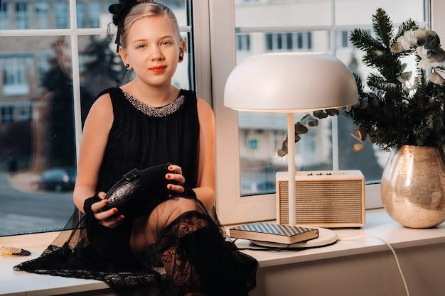 검은 드레스를 입은 세련된 소녀가 손에 지갑을 들고 창가 창턱에 앉아 있습니다.
