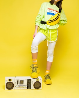Стильная девушка в ярко-салатовой футболке и шортах, белых леггинсах, желтых кроссовках и носках поставила ногу на ретро магнитофон. вертикальное фото