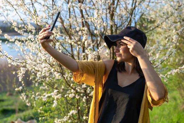 모자에 세련된 소녀가 숲의 꽃 피는 나무 근처에서 일몰 셀카를 만듭니다.