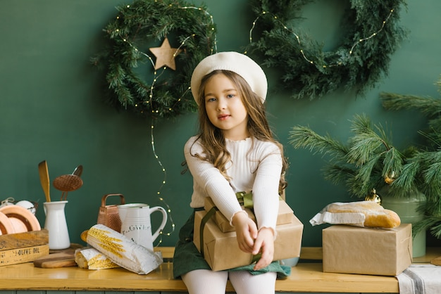 Стильная девушка в белом берете сидит на стильной кухне, украшенной к рождеству и новому году изумрудом или зеленью. рождественские венки на стене. девушка держит рождественский подарок