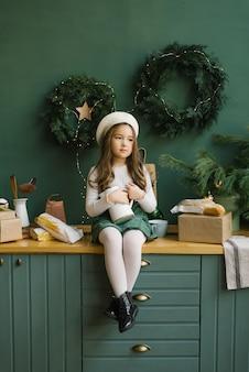 Стильная девушка в белом берете сидит на стильной кухне, украшенной к рождеству и новому году изумрудом или зеленью. рождественские венки на стене. девушка держит белый кувшин