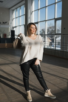 둥근 안경, 검은 바지, 가벼운 스웨터를 입은 세련된 소녀가 큰 창문을 배경으로 방 바닥에 선다.
