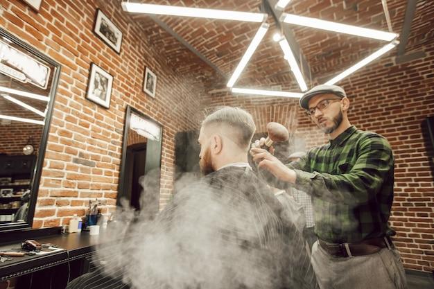 Стильный парикмахер в парикмахерской чистит шею клиентке щеткой и специальной пудрой.