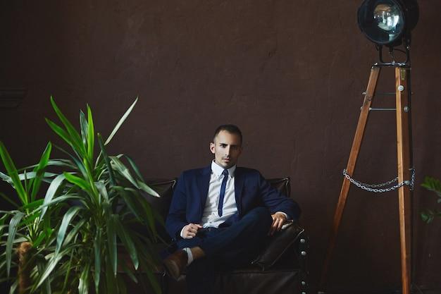 Стильный красивый молодой человек в модном синем костюме сидит на диване в темном интерьере