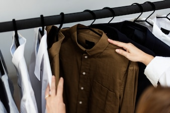 A stylish is choosing cloth from the rack