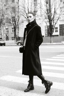 ストリートの黒のロングコートを着たスタイリッシュなモデル。