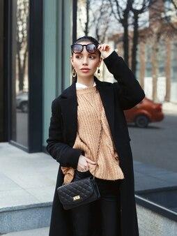 Стильная модель в черном длинном пальто на улице.