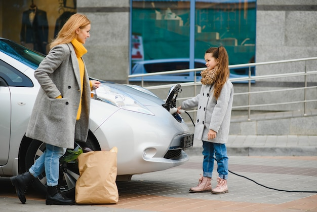 Стильная мама учит дочь, как правильно заряжать электромобиль