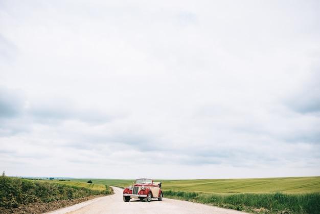 Стильный красный ретро автомобиль на полевой дороге
