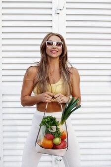 Стильная стройная женщина в спортивной одежде и солнечных очках с сумкой, полной овощей и фруктов. концепция здорового питания. здоровый образ жизни, экология, вегетарианство.