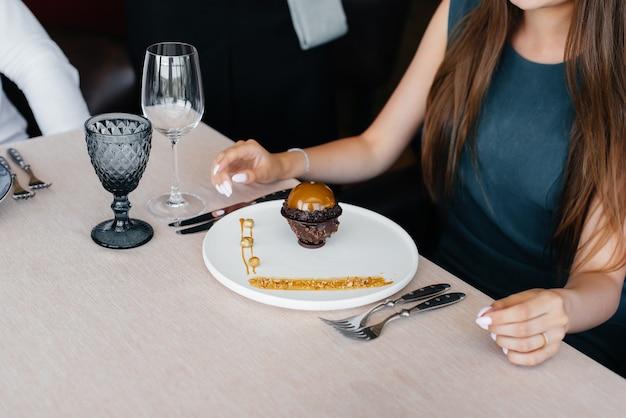 앞치마를 두른 세련된 웨이터가 고급 레스토랑에서 어린 소녀를 섬기고 음식 금으로 덮인 독특한 디저트를 그녀에게 제공합니다. 고객 서비스.