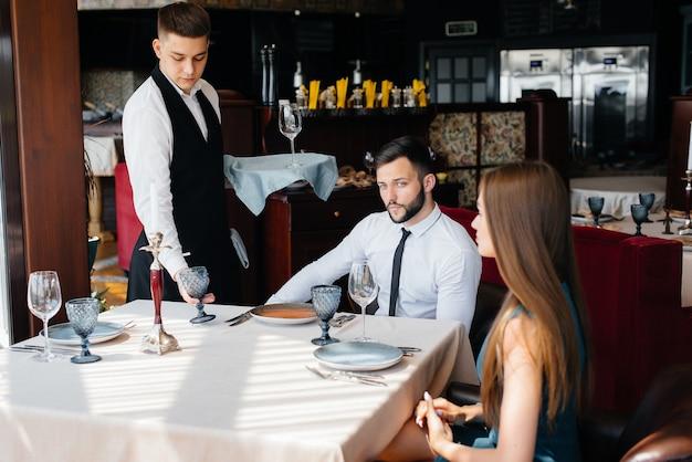 세련된 웨이터는 미식가 레스토랑에서 데이트를 한 젊은 커플에게 서비스를 제공합니다. 케이터링에서 고객 서비스.