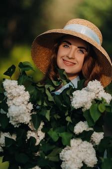 麦わら帽子をかぶったスタイリッシュな女性が、サニースプリングパークのライラックの花にポーズをとっています。春の庭にライラックの花束を持って立っている美しい少女の穏やかな肖像画。