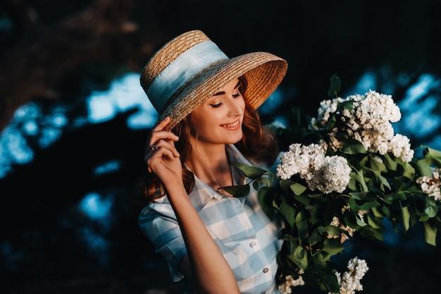 サニースプリングパークで、麦わら帽子をかぶったスタイリッシュな女性がライラックの花束を持ってポーズをとっています。春の庭に立っている美しい少女の静かな肖像画。
