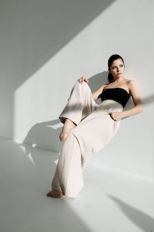 흰 바지와 검은색 티셔츠를 입은 세련된 여성이 흰 벽에 기대어 성장했다