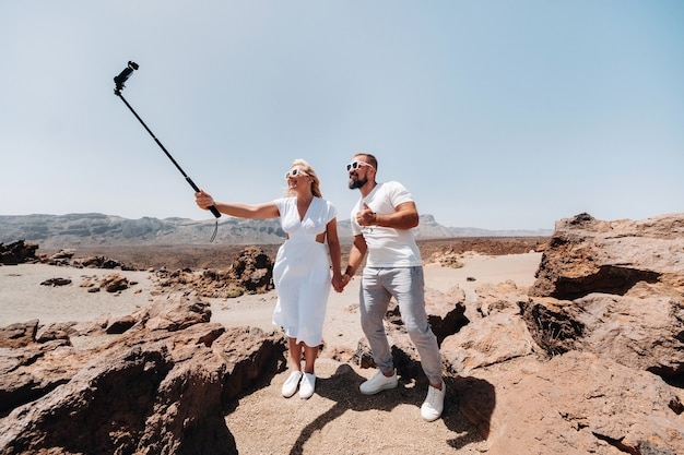 Стильная женщина делает селфи в кратере вулкана тейде. пейзаж пустыни на тенерифе. национальный парк тейде. пустынный кратер вулкана тейде. тенерифе, канарские острова.