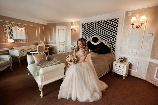 Стильная молодая невеста в роскошном свадебном платье сидит на кровати в красивом винтажном интерьере ...