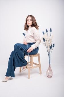 カジュアルな服を着たスタイリッシュな若い女の子は、彼女の手にドライフラワーと肘掛け椅子に座っています