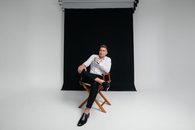 В режиссерском кресле на черном фоне сидит стильный молодой человек в белой рубашке. красивый харизматичный бизнесмен.