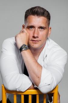 Стильный молодой человек в белой рубашке сидит в режиссерском кресле на черном фоне. красивый харизматичный бизнесмен.