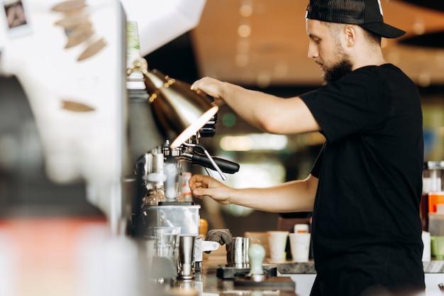 Стильный молодой человек с бородой, одетый в повседневную одежду, варит кофе в кофеварке в уютной кофейне. .