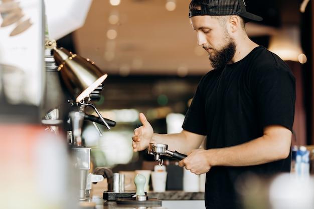 Стильный молодой человек с бородой, одетый в повседневную одежду, готовит кофе в кофеварке в современной кофейне. .