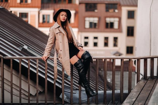 ベージュのコートと黒い帽子をかぶったスタイリッシュな若い女性が市内中心部の屋上に座っています