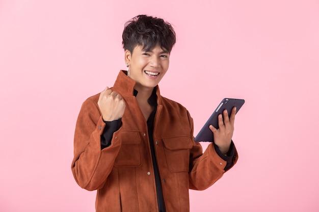 성공적이고 기쁨을 표현하는 아시아 남자는 분홍색 공백 복사 공간 스튜디오 배경에서 격리된 사랑에 빠진 카메라를 바라보는 옆 눈에 태블릿을 사용하는 잘생긴 젊습니다.