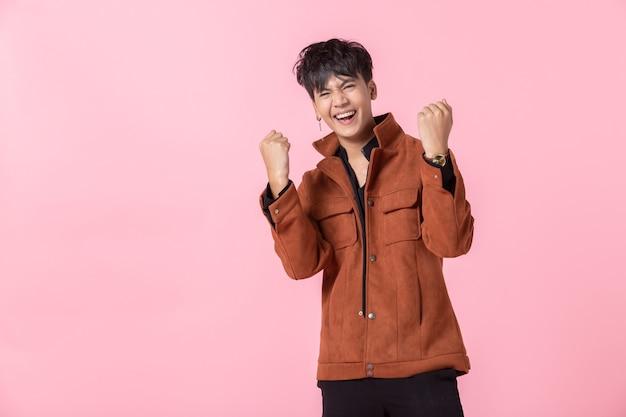 성공적이고 기쁨을 표현하는 아시아 남자는 두 손을 가진 잘생긴 젊고 분홍색 빈 카피 공간 스튜디오 배경에서 격리된 사랑에 빠진 카메라를 바라보는 옆 눈을 보여줍니다.