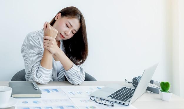 Успешная бизнес-леди сидит в офисе использует ноутбук для работы так много, что у нее болят запястья.