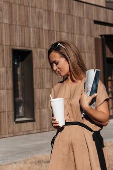 Успешная деловая женщина. стиль деловой женщины. в руках журнал и кофе.
