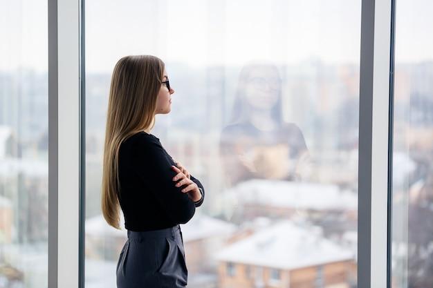 Успешная женщина-менеджер в собственном офисе с большими окнами стоит и смотрит на город. деловая женщина в очках на фоне больших окон