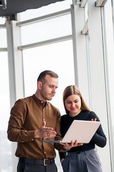 Успешная офисная работница с коллегой с нетбуком стоит в небоскребе на фоне окна с видом на город. городские архитекторы, глядя на ноутбук, довольны проектом