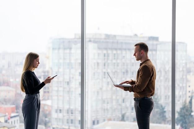넷북을 가지고 있는 동료와 함께 성공한 여성 회사원은 도시가 내려다보이는 창문을 배경으로 고층 빌딩에 서 있습니다. 프로젝트에 만족하는 노트북을 보고 있는 도시 건축가
