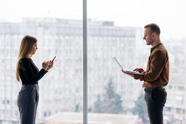 ネットブックを持った同僚と一緒に成功した女性サラリーマンが、街を見下ろす窓を背景に高層ビルに立っています。プロジェクトに満足しているラップトップを見ている都市建築家