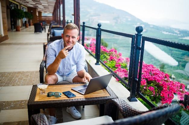 成功した男性実業家はラップトップを持ってテーブルに座っており、彼は休暇で働いています。休暇と在宅勤務。男はパノラマの景色を望むテラスのレストランに座っています