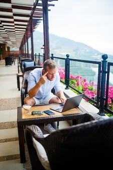 성공적인 남성 사업가 노트북 테이블에 앉아, 그는 휴가에 노력하고 있습니다. 휴가 및 원격 근무. 그 남자는 탁 트인 전망이있는 테라스에있는 레스토랑에 앉아 있습니다.
