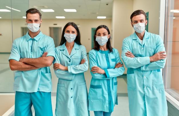 В коридоре клиники стоит успешная бригада врачей в защитных медицинских масках. защита в карантине и covid-19.
