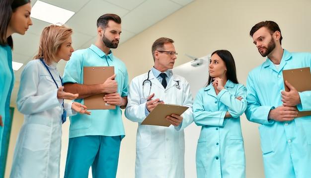 Успешная команда врачей с историей болезни всерьез обсуждает методы лечения, стоя в коридоре клиники. пожилой врач обучает интернов.