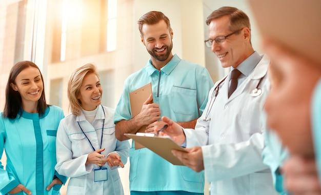 Успешная команда врачей с записями пациентов обсуждает лечение, стоя в коридоре клиники. молодой врач обучает молодых интернов.