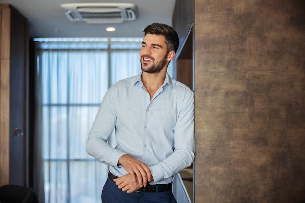 Успешный молодой красавец в строгой рубашке и брюках смотрит в сторону с улыбкой