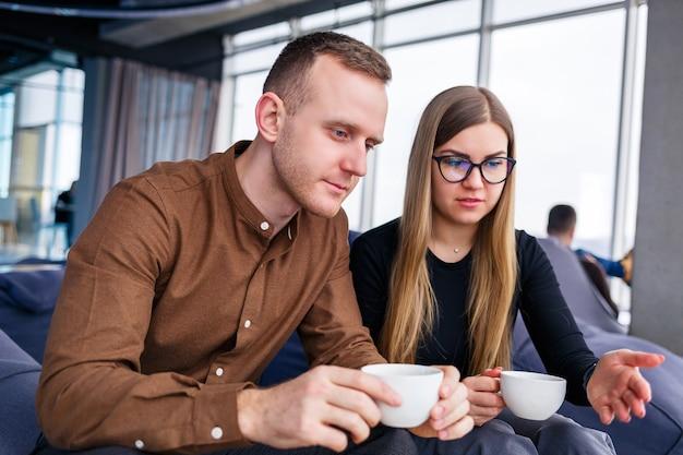 Успешная молодая женщина-менеджер со своим боссом сидит с ноутбуком на мягком кресле у панорамного окна и пьет кофе. деловая женщина и мужчина работают над новым проектом