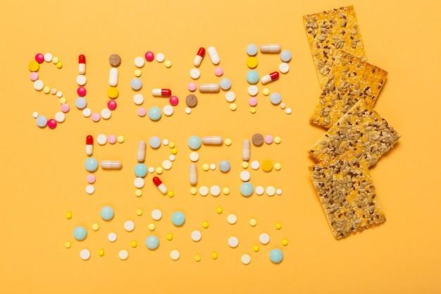 무설탕 단어는 다채로운 알약과 씨앗이 포함된 건강한 식사 쿠키, 건강한 생활 방식을 위한 당뇨병 약으로 작성됩니다. 사람들을 위한 특별 대우의 상징입니다.