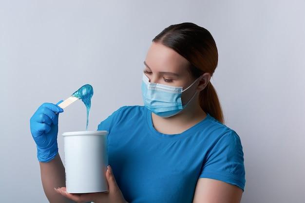 파란색 장갑과 의료용 마스크를 쓴 설탕 마스터가 파란색 설탕 왁스 스틱을 들고 있습니다. 탈모 및 미용 개념.