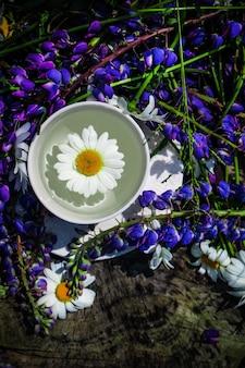 여름 아침, 하얀 커피 한 잔과 야생화 꽃다발 프리미엄 사진