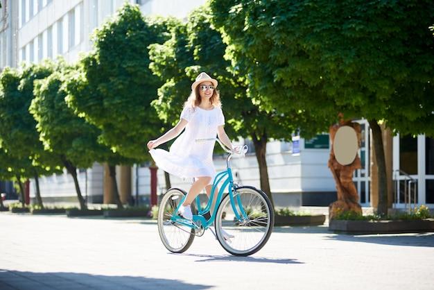 햇볕이 잘 드는 여자는 파란색 복고풍 자전거에 햇볕에 타고있다