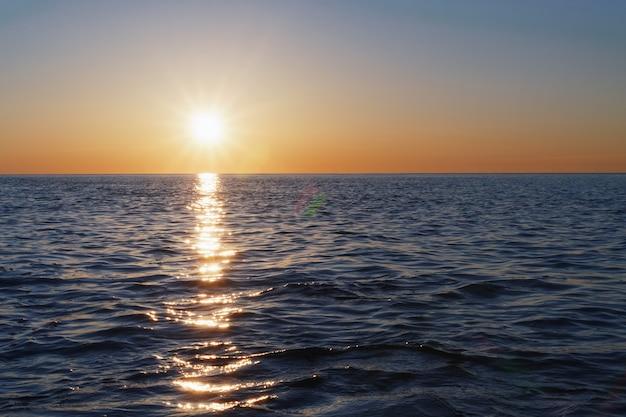 수평선으로 뻗어있는 바다의 햇살이 내리 쬐는 석양이 바다를 볼 수 있습니다.
